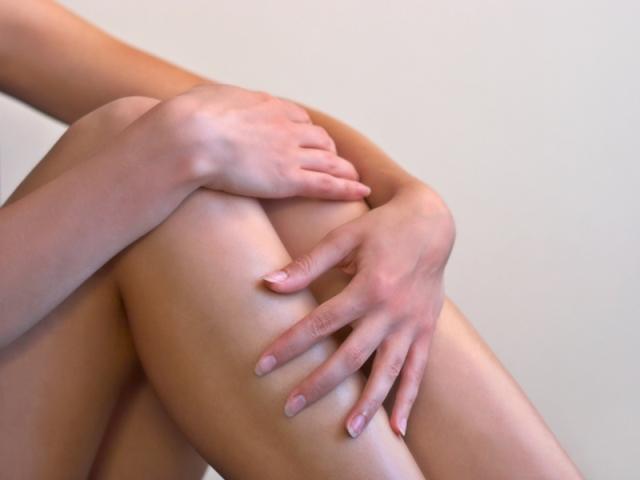 Женщина держится за колени