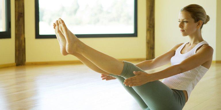 Девушка делает растяжку ног для профилактики варикоза ног
