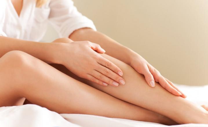 Девушка массирует свои ноги после нанесения крема