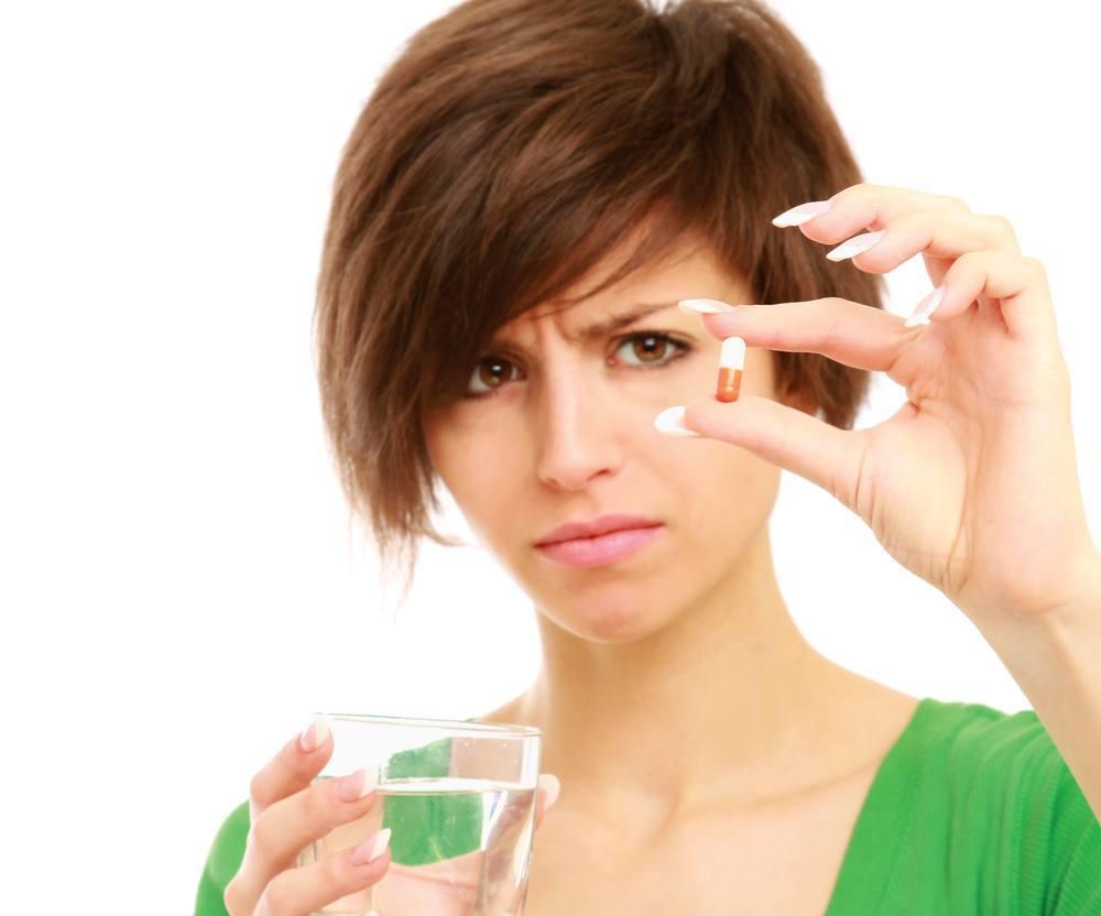 Девушка со стаканом воды принимает лекарства