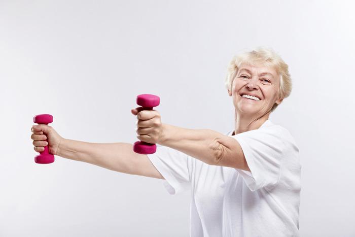 Пожилая женщина поднимает гантели